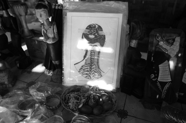 A souvenir stall at Nai Soi village. The diagram shows how the collar bone and rib cage are pushed down by the rings to create the illusion of a long neck.